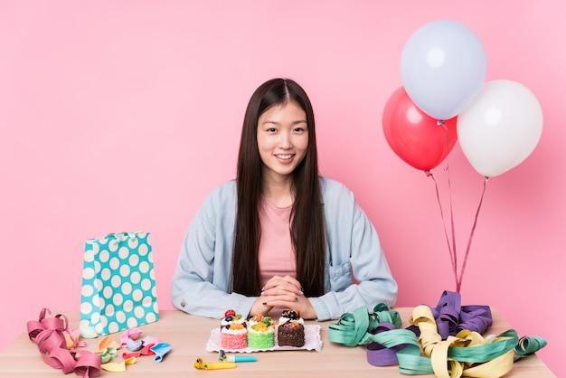 De jonge chinese vrouw die een verjaardag organiseert isoleerde gelukkig, glimlachend en vrolijk.