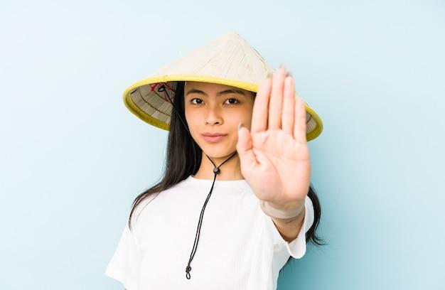 De jonge chinese vrouw die een vietnamese geïsoleerde hoed draagt verward, voelt twijfelachtig en onzeker.