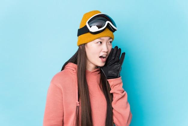 De jonge chinese vrouw die skikleren draagt isoleerde het schreeuwen en palm houden dichtbij geopende mond.