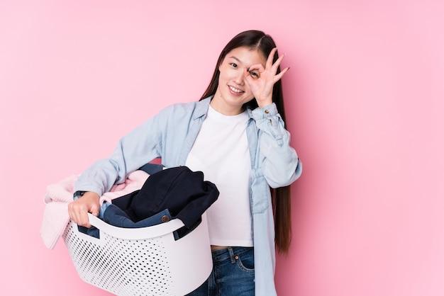 De jonge chinese vrouw die vuile kleren opneemt isoleerde opgewekt houdend ok gebaar op oog.
