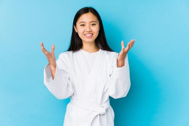 De jonge chinese vrouw het praktizeren karate isoleerde het ontvangen van een prettige verrassing, opgewekte en opheffende handen.