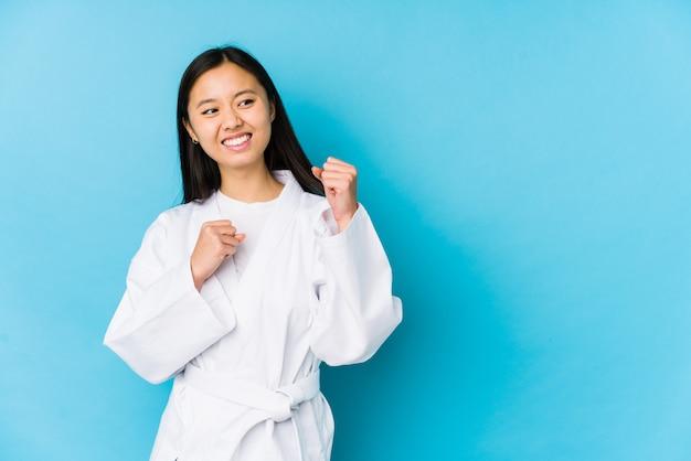 De jonge chinese vrouw het praktizeren karate isoleerde het opheffen van vuist na een overwinning, winnaarconcept.