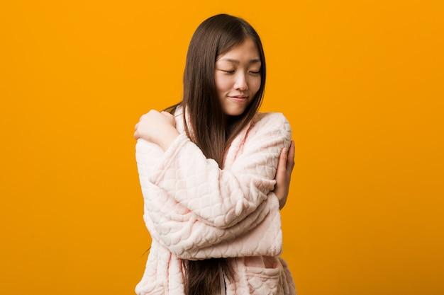 De jonge chinese vrouw in pyjama koestert zich, onbezorgd en gelukkig glimlachen.