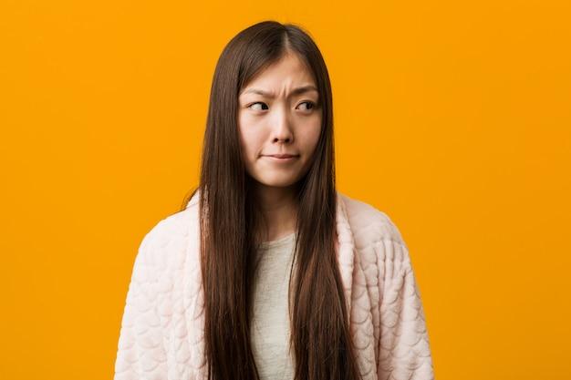 De jonge chinese vrouw in verwarde pyjama, voelt twijfelachtig en onzeker.