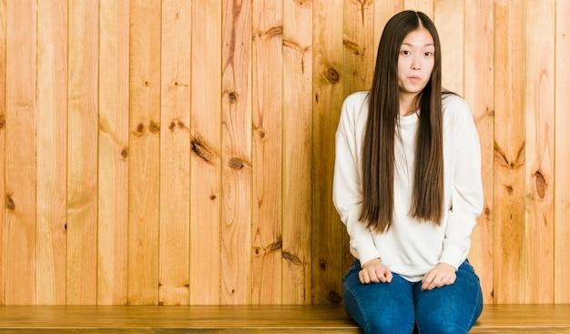 De jonge chinese vrouwenzitting op een houten plaats haalt schouders en open verwarde ogen op.