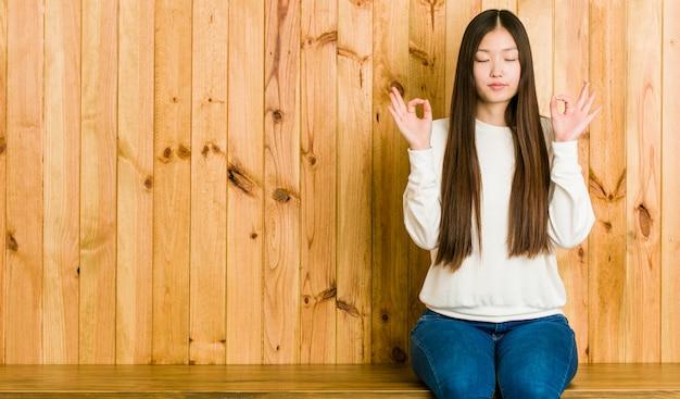 De jonge chinese vrouwenzitting op een houten plaats ontspant na harde werkdag, voert zij yoga uit.