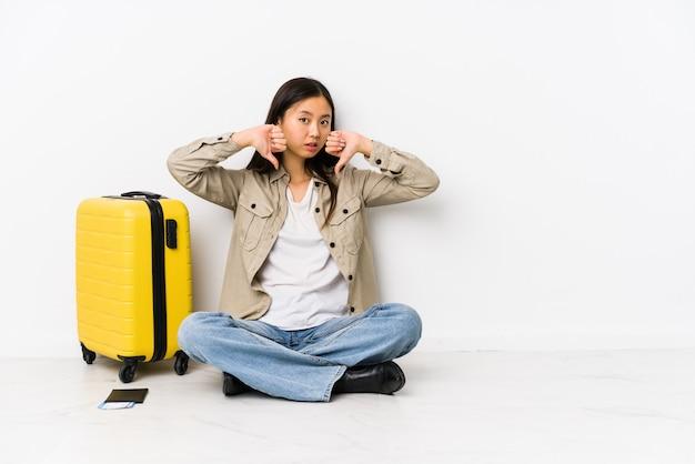 De jonge chinese zitting die van de reizigersvrouw een instapkaarten houden die duim tonen neer en afkeer uitdrukken.