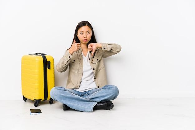 De jonge chinese zitting die van de reizigersvrouw een instapkaarten houden die duimen tonen en duimen neer