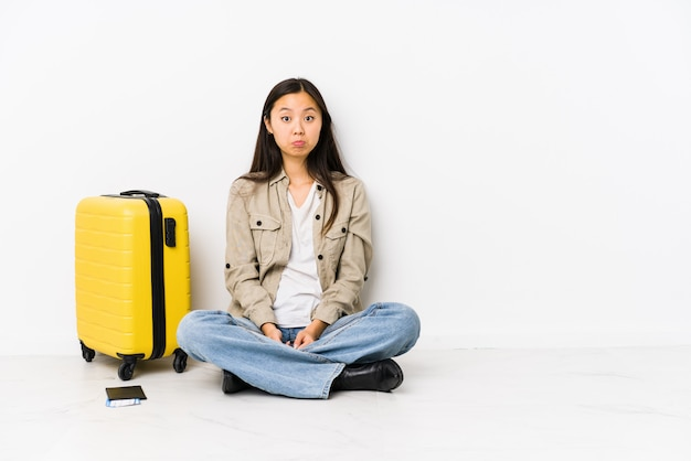 De jonge chinese zitting die van de reizigersvrouw een instapkaarten houden haalt schouders en open ogen op verward.