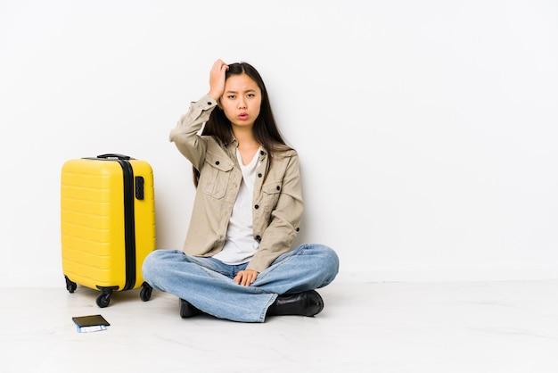 De jonge chinese zitting die van de reizigersvrouw een instapkaarten houden vermoeid en zeer slaperig houdend hand op hoofd.