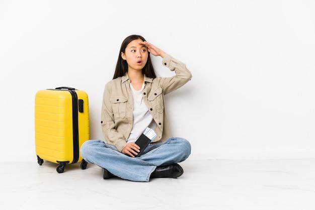 De jonge chinese zitting die van de reizigersvrouw instapkaarten houden die ver weg het houden van hand op voorhoofd houden.