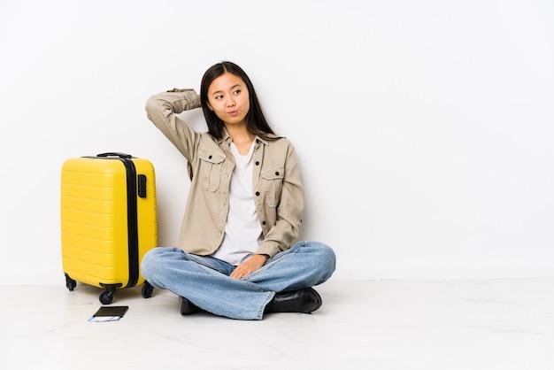 De jonge chinese zitting die van de reizigersvrouw instapkaarten houdt