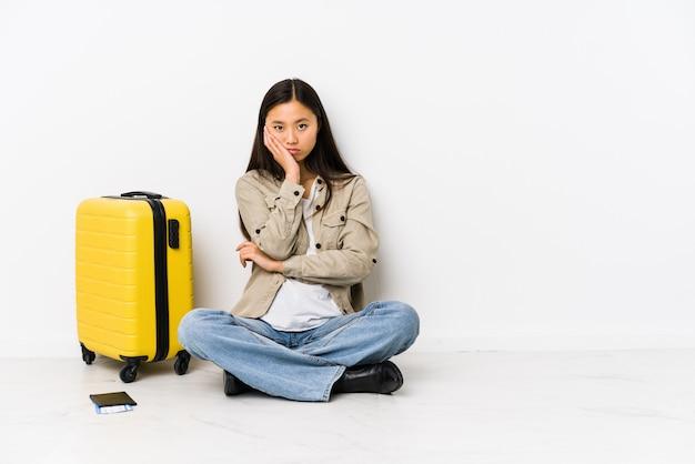 De jonge chinese zitting die van de reizigersvrouw verveeld, vermoeid instapkaarten houden en een ontspannen dag nodig hebben.