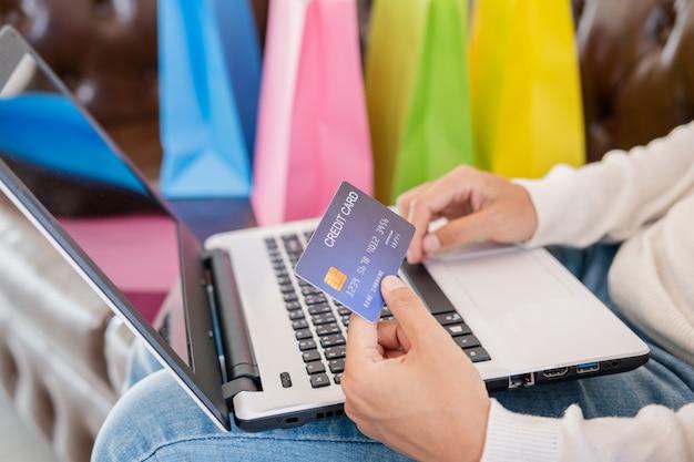De jonge creditcard van de vrouwenholding en het gebruiken van laptop met het winkelen zak, online betalingsconcept
