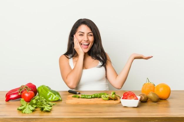 De jonge curvy vrouw die een gezonde maaltijd voorbereidt houdt iets op een palm