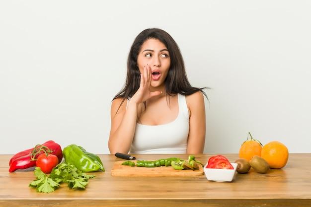 De jonge curvy vrouw die een gezonde maaltijd voorbereidt zegt een geheim heet remmend nieuws en kijkt opzij