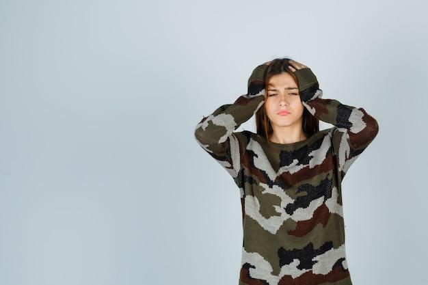 De jonge dame die het hoofd omklemt met dient sweater in en kijkt teleurgesteld