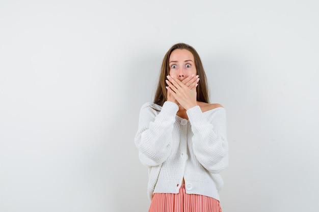 De jonge dame die mond behandelt dient cardigan en rok in verwarring geïsoleerd te kijken