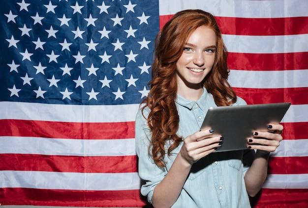De jonge dame die van de roodharige zich over de vlag van de vs bevindt die tablet gebruikt
