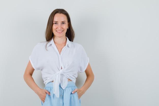 De jonge dame die zich bevindt met dient zak in blouse en rok in en kijkt optimistisch