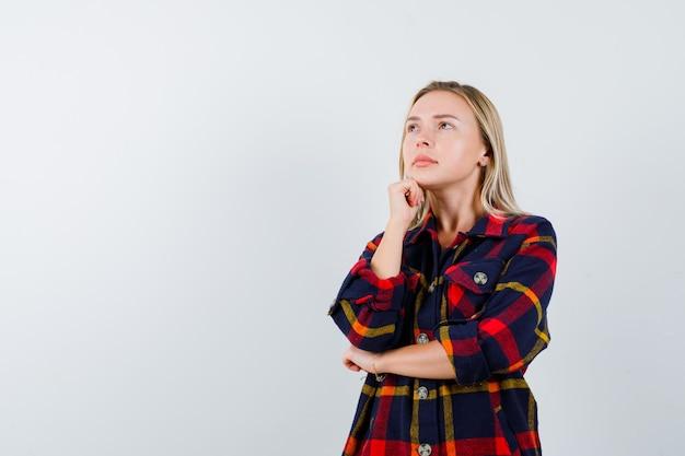 De jonge dame die zich in het denken bevindt stelt in geruit overhemd en kijkt peinzend, vooraanzicht.