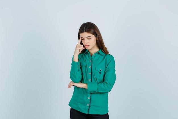 De jonge dame die zich in het denken bevindt stelt in groen overhemd en kijkt verontrust. vooraanzicht.