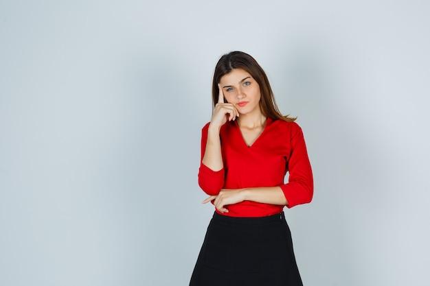 De jonge dame die zich in het denken bevindt stelt in rode blouse, rok en peinzend kijkt