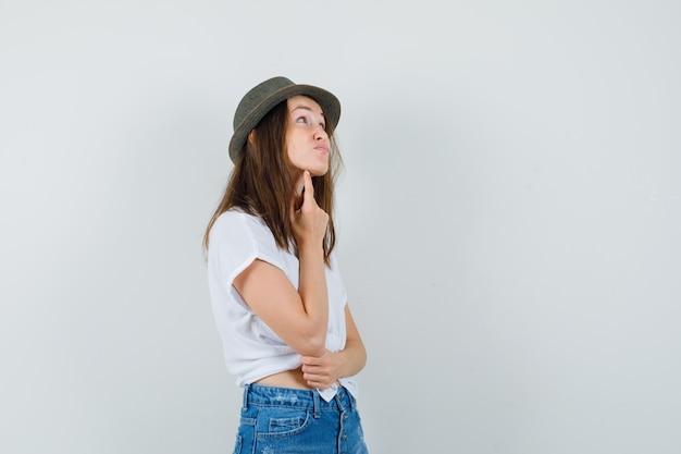 De jonge dame die zich in het denken bevindt stelt in t-shirt, spijkerbroek, hoed en kijkt aarzelend, vooraanzicht.