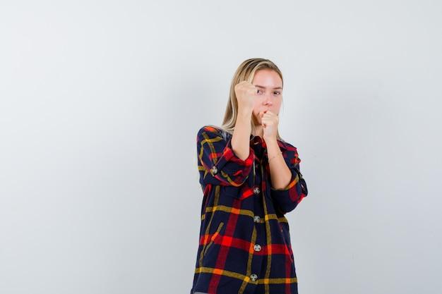 De jonge dame die zich in strijd bevindt stelt in geruit overhemd en kijkt zelfverzekerd, vooraanzicht.
