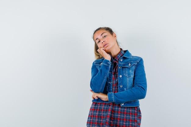 De jonge dame dient de leunende wang in overhemd, jasje en ziet er schattig uit. vooraanzicht.