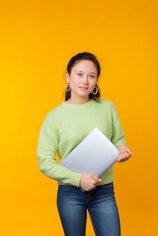De jonge dame houdt haar laptop op geel