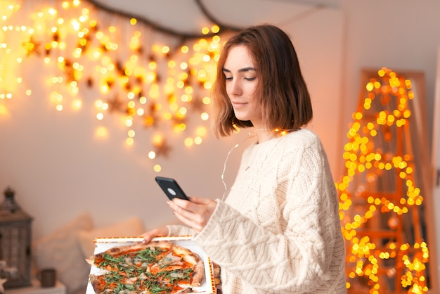 De jonge dame houdt thuis een telefoon en een pizza vast.