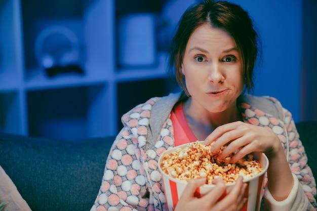 De jonge dame kijkt tv lachend en eet popcorn die pret heeft alleen thuis genietend van moderne televisie.