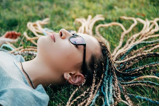 De jonge dame met doosvlechten ligt op gras met gesloten ogen
