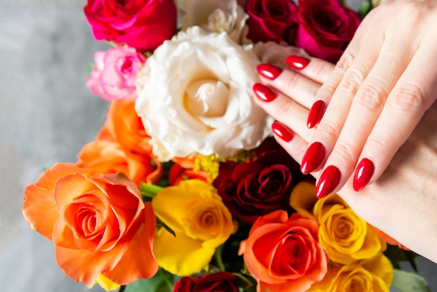 De jonge dame toont haar rode manicurespijkers