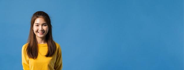 De jonge dame van azië met brede glimlach, kleedde zich in vrijetijdskleding en bekijkt camera over blauwe achtergrond. gelukkige schattige blije vrouw verheugt zich over succes. panoramische bannerachtergrond met exemplaarruimte.