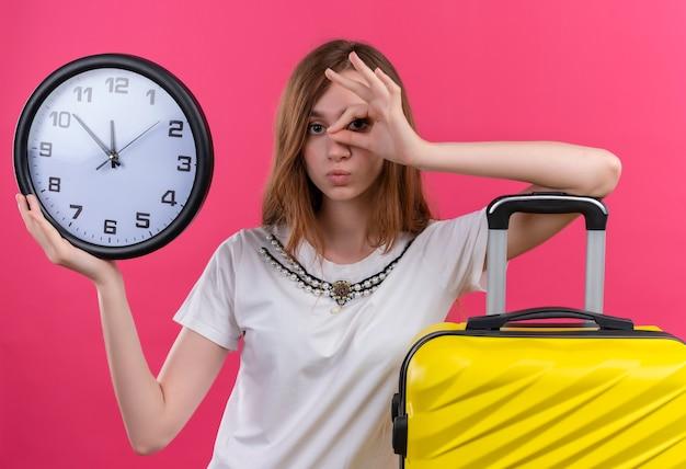 De jonge de holdingsklok die van het reizigersmeisje blikgebaar doet en wapen op koffer op geïsoleerde roze muur zet