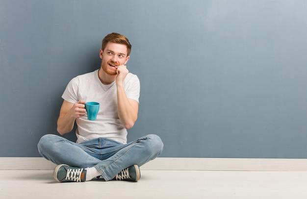 De jonge de mensenzitting van de roodharigestudent op de vloer ontspande het denken over iets bekijkend een exemplaarruimte. hij houdt een koffiemok vast.