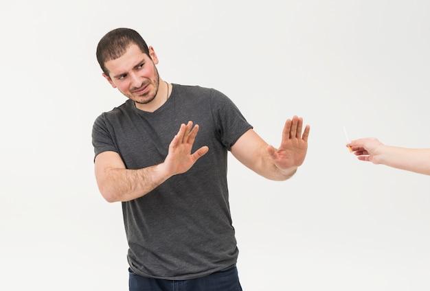 De jonge die mens zegt nr aan sigaret door een persoon wordt aangeboden op witte achtergrond wordt geïsoleerd