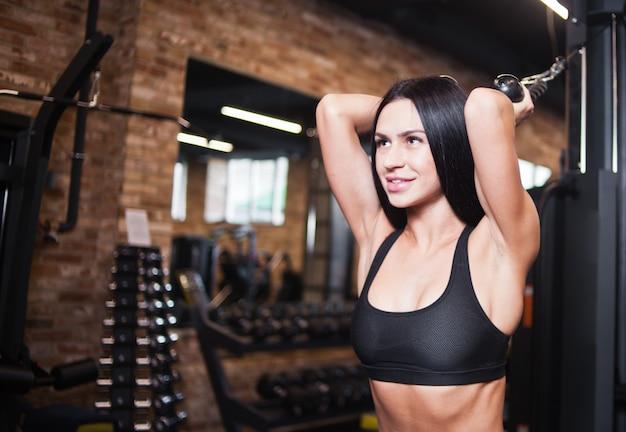 De jonge donkerbruine geschikte vrouw voert oefening voor triceps met oefeningsmachine uit in gymnastiek