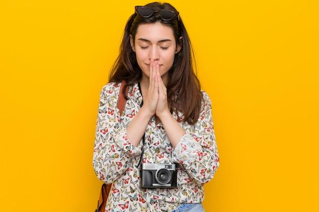De jonge donkerbruine holding van de reizigersvrouw dient bidt dichtbij mond in, voelt zeker.