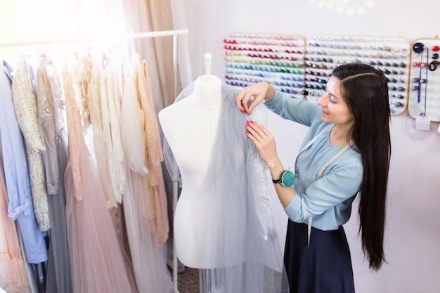 De jonge donkerbruine naaister meet mooie stof op wit model in haar workshop