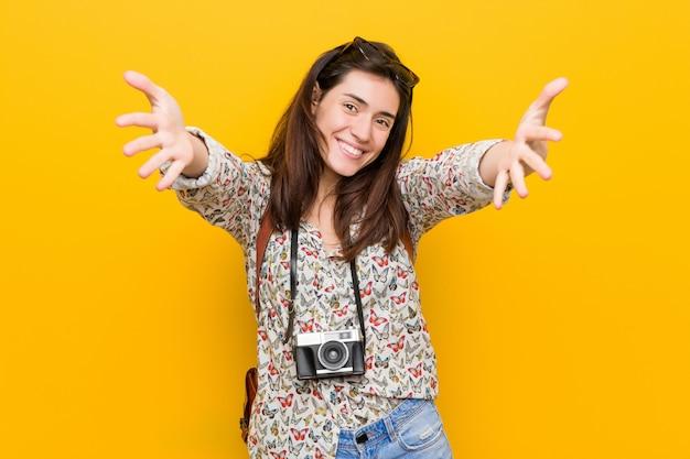 De jonge donkerbruine reizigersvrouw voelt zich zeker die een omhelzing geven aan de camera.