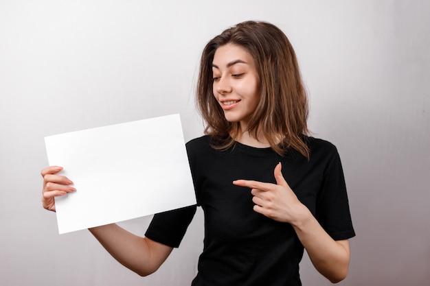 De jonge donkerbruine vrouw in het zwarte t-shirt glimlachen toont een wit blad op een witte ruimte. copyspase