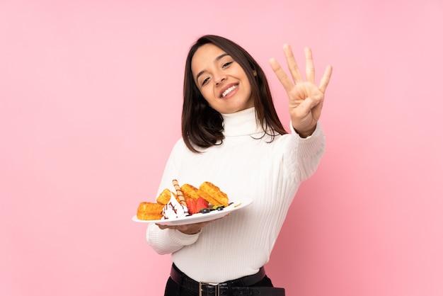 De jonge donkerbruine wafels van de vrouwenholding op geïsoleerde roze gelukkig en vier tellen met vingers