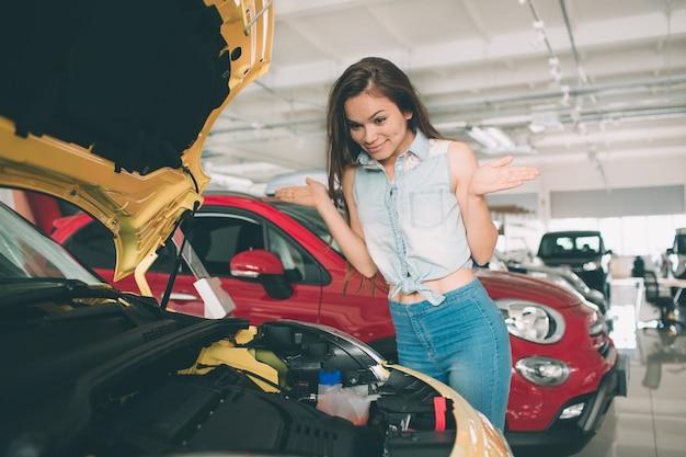 De jonge donkerharige vrouw onderzoekt auto bij de dealer en maakt zijn keuze.