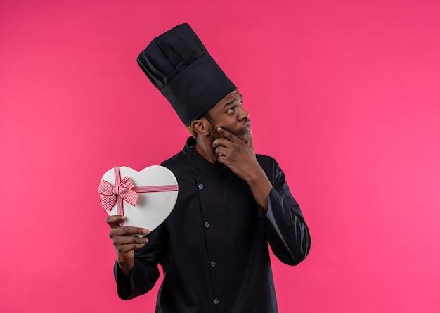 De jonge doordachte afro-amerikaanse kok in eenvormige chef-kok houdt de doos van de hartvorm die op roze muur wordt geïsoleerd