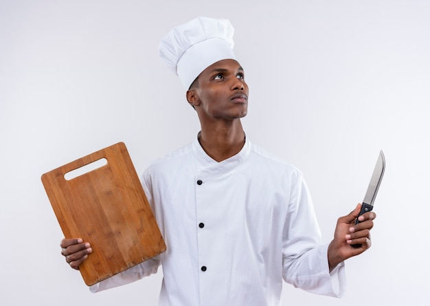 De jonge doordachte afro-amerikaanse kok in eenvormige chef-kok houdt houten die keukenbureau en mes op witte muur wordt geïsoleerd