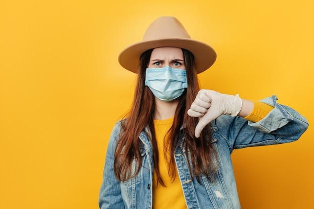 De jonge droevige vrouw die in hoed afkeurend camera bekijken die duim tonen neer, draagt medisch gezichtsmasker en denimjasje, dat over gele studioachtergrond wordt geïsoleerd.