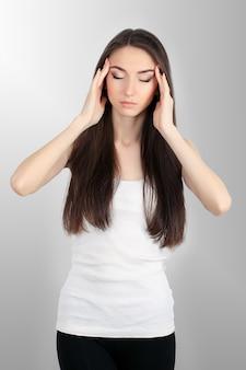 De jonge droevige vrouw raakt het voorhoofd en voelt sterke hoofdpijn
